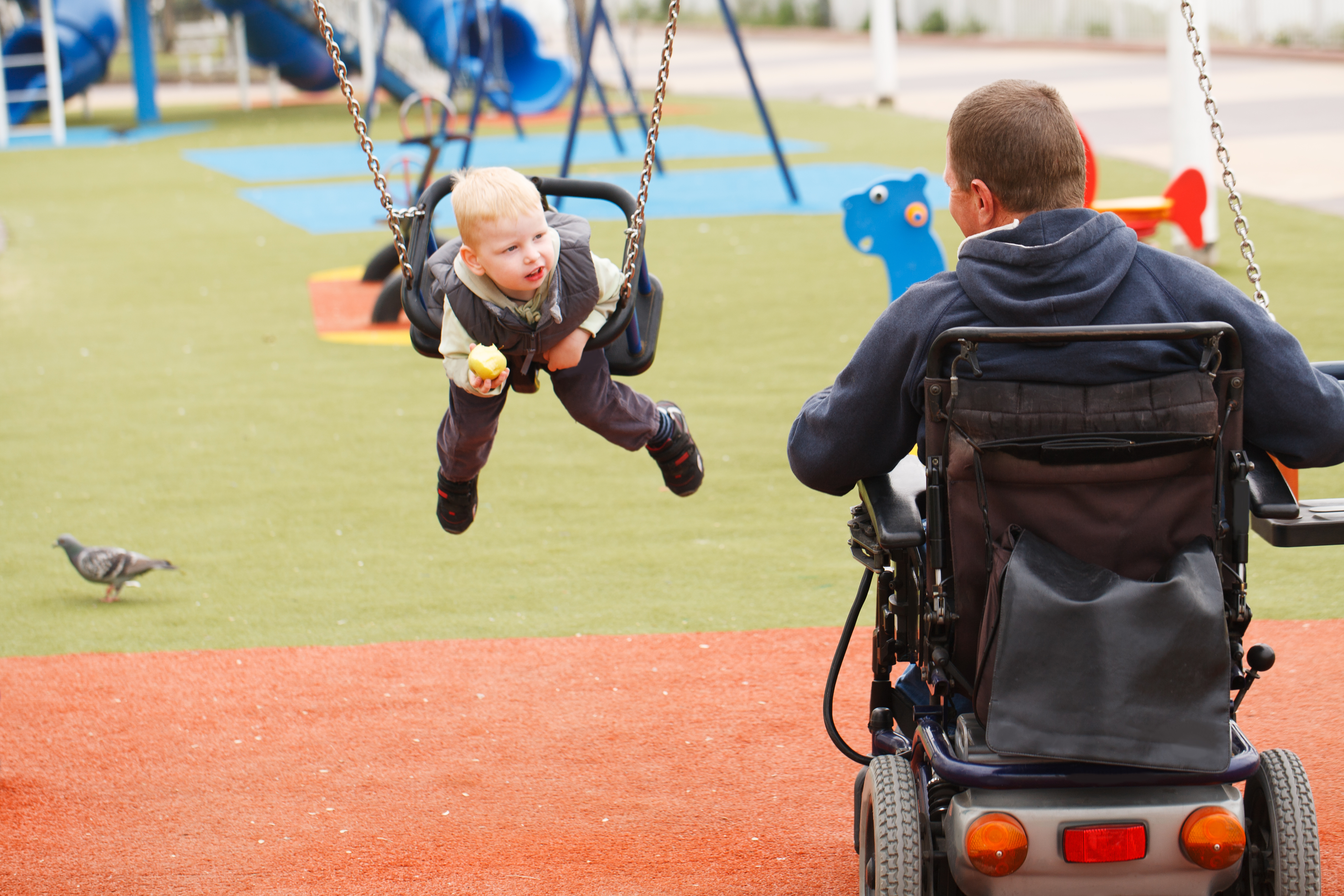 Man in wheelchair pushing his child on the swing